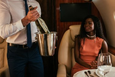 cropped view of air steward holding champagne bucket and bottle near elegant african american woman