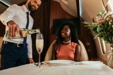 selective focus of handsome air stewards pouring champagne into glass near smiling african american woman in private plane