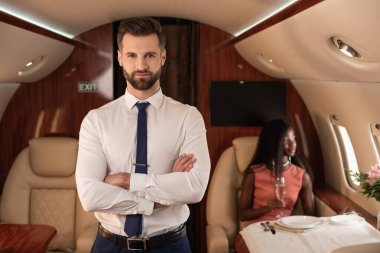handsome air steward with crossed arms looking at camera near elegant african american woman in private plane