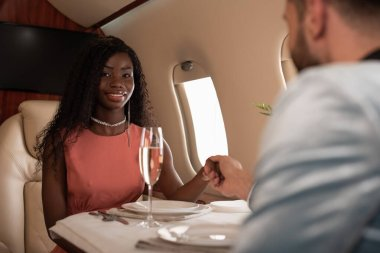 Selective focus of elegant african american girl looking at camera while holding hands with man at served table in private plane stock vector
