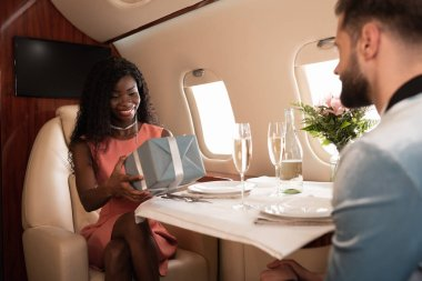 Selective focus of happy african american girl holding gift box near man and served table in private plane stock vector