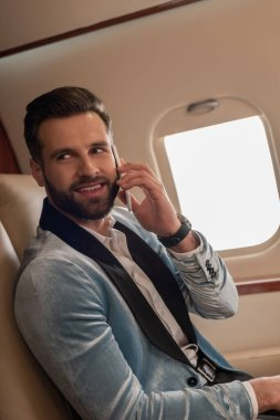 Handsome, elegant man smiling while talking on smartphone in private jet stock vector
