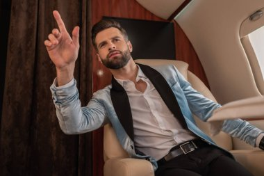 elegant, confident man showing come gesture while calling for air steward in private jet