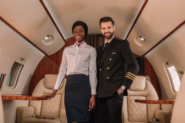 handsome, positive pilot standing with hand in pocket near smiling african american stewardess in private jet