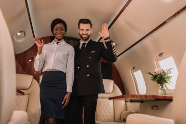 happy pilot and smiling afican american stewardess waving hands while looking at camera in private jet