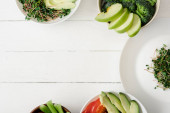 Fotografie top view of fresh vegetables and fruits with microgreen in bowls on white wooden surface