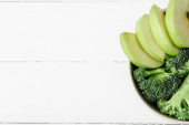 top view of fresh green apple and broccoli in bowl on white wooden surface