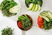 top view of fresh vegetables and fruits with microgreen in bowls on white wooden surface