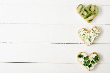Top view of heart shaped canape with creamy cheese, microgreen, parsley and kiwi on white wooden surface stock vector
