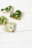 střapec ve tvaru srdce se smetanovým sýrem, brokolicí, mikrozelenou, petrželkou a kiwi na bílém dřevěném povrchu