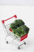fresh green broccoli in shopping cart on white wooden surface
