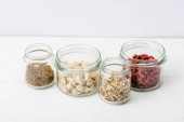 goji berries and sprouts in glass jars on white wooden surface