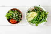 top view of fresh vegetables with avocado and microgreen in bowls on white wooden surface