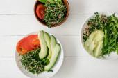 felülnézet friss zöldségek avokádó és mikrozöld tálak fehér fa felületen