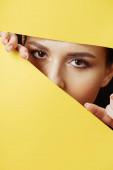 Nő nézi kamera a lyukon keresztül, és megérinti sárga papír ujjakkal
