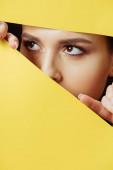 Nő néz át a lyukon, és megérinti sárga papír ujjaival