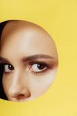 Dívka s kouřovýma očima dívá na kameru přes díru ve žlutém papíru