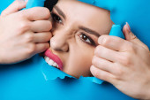 Woman with pink lips and smoky eyes touching and biting ripped blue paper across hole