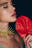 Woman holding red anthurium near leaves isolated on black