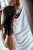 Ausgeschnittene Ansicht eines Sportlers im schwarzen Boxhandschuh im Sportzentrum
