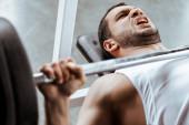selektivní zaměření emocionální sportovec cvičení s činkou v tělocvičně