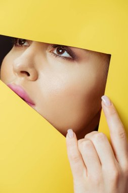 Woman looking across triangular hole and touching yellow paper stock vector