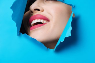 Happy woman with pink lips smiling across ripped blue paper