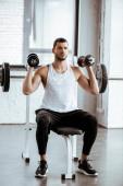atletický muž drží činky při cvičení v blízkosti činky v tělocvičně