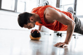 Photo athletic sportsman doing plank exercising with ball