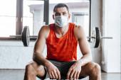 Fényképek atlétikai sportoló orvosi maszkban ül közelében súlyzó tornaterem