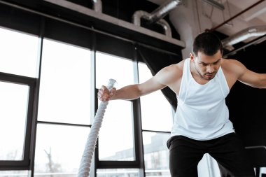 concentrated man exercising with battle rope in gym