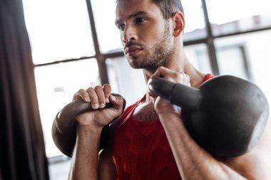 Ağır dambıllarla egzersiz yapan atletik sporcuların seçici odağı
