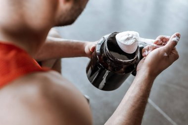 Cropped view of sportsman holding jar and measuring spoon with protein powder stock vector