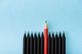 Horní pohled na červenou tužku mezi černými na modrém pozadí