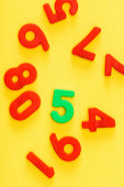 Photo Top view of unique green five number among red on yellow