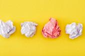 Horní pohled na jedinečné zmačkaný růžový papír mezi bílými na žlutém pozadí