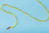 High angle view of chain with unique red and yellow paper clips on blue