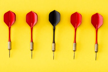 Flat lay with black dart among red on yellow