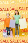rozkošné usměvavé děti drží nákupní tašky na žluté, prodej ilustrace