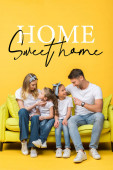 Fotografie happy parents talking with adorable daughter and son while sitting together on sofa on yellow, home sweet home illustration