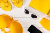 Horní pohled na sluneční brýle, žluté plavky se slunečním kloboukem a smartphonem na bílém dřevěném povrchu