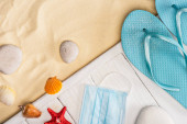 Top view of blue flip flops near medical mask and seashells on white wooden planks and sand