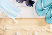 Pohled shora na lékařskou masku, žabky a sluneční brýle na bílých dřevěných prknech u oblázků na písku