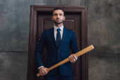Photo Angry collector holding baseball bat near door in room