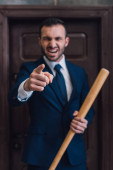 Photo Selective focus of angry collector with baseball bat pointing with finger and shouting near door in room