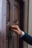 Teilansicht des Sammlers, der mit der Hand an die Tür klopft