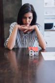 Aufgebrachte und nachdenkliche Frau mit geballten Händen am Tisch mit Hausmodell in der Nähe von Dokument im Zimmer