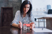 Photo Concentrated woman putting hands near house model with paper and pen on table in room