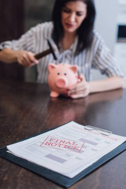 Selective focus of woman holding hammer above piggy bank at table with documents with final notice lettering in room stock vector
