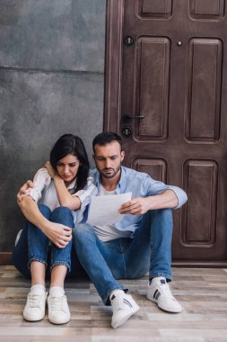 Husband reading document and hugging stressed wife near wall on floor